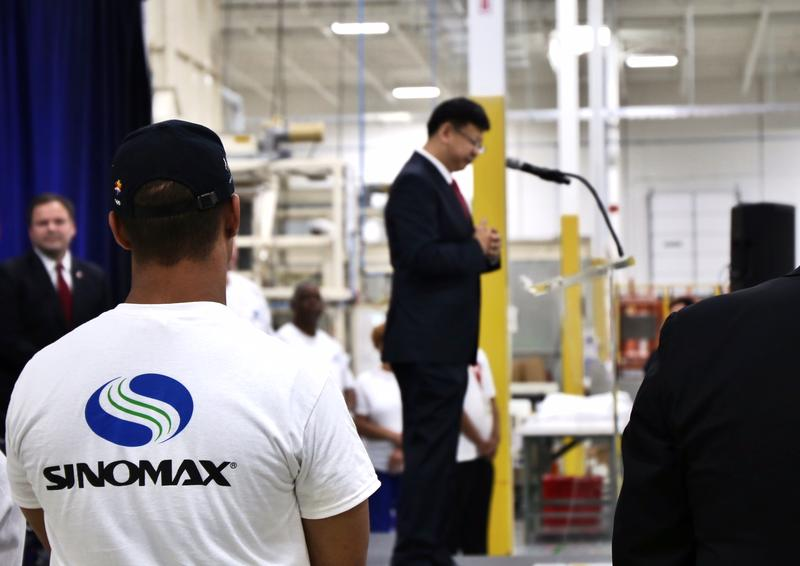 A worker looks on as Sinomax president and CEO Frank Chan introduces them to the new factory.