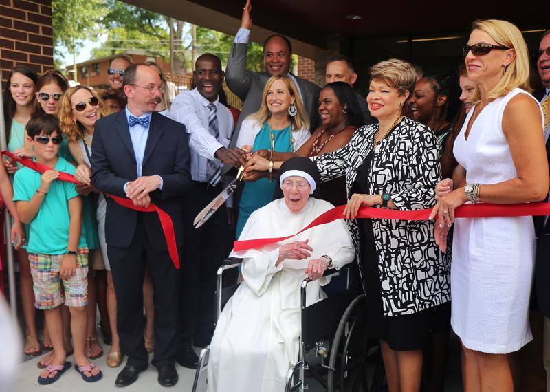 Nashville Mayor Megan Berry, accompanied by government representatives, future tenants, and the late George Barrett's family, whom the building is named after, cut the ribbon for the new Envision Cayce housing unit in East Nashville.