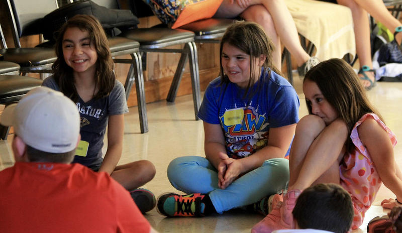 Alissa Scott, left, sits with other campers during a music session at Camp Evergreen. The three-day camp is designed to help children manage the mourning process.