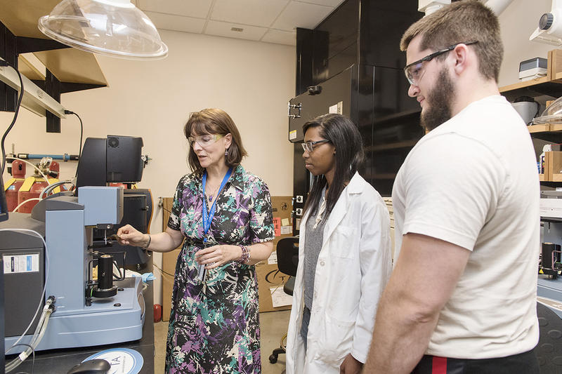 Chemistry professor Andrienne Friedli, left, shows MTSU undergraduates Jack Lasseter and Kenya King liquid crystals in a laboratory.
