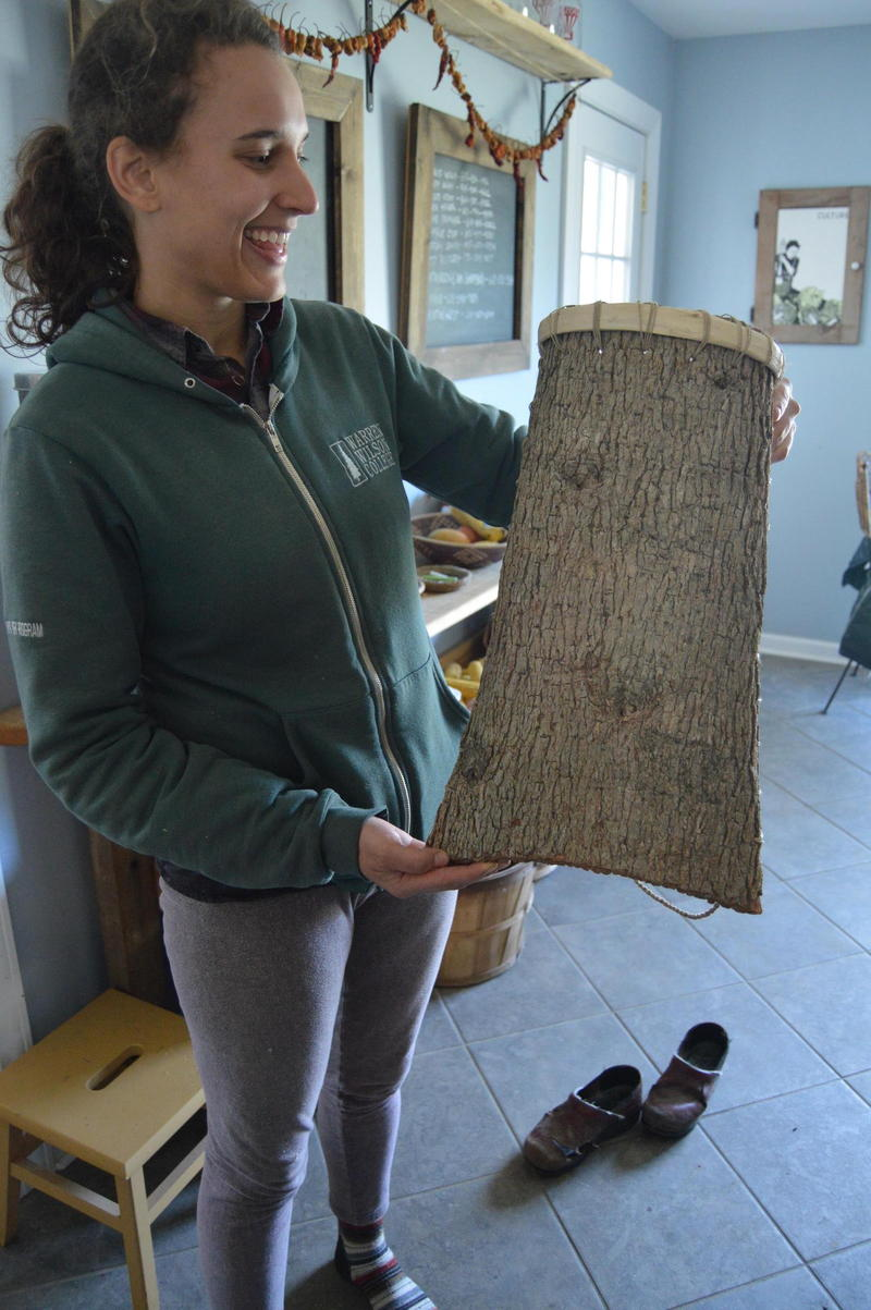 Heather Sevcik shows off a tree-bark container made from trees on her farm.