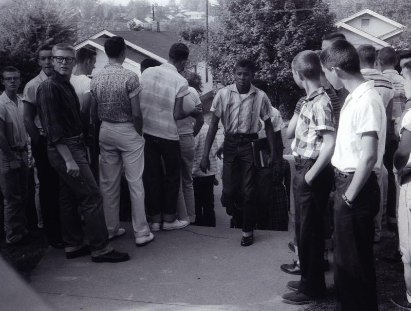 Bobby Cain steps into Clinton High School the first day of class in 1956 as white students look on.