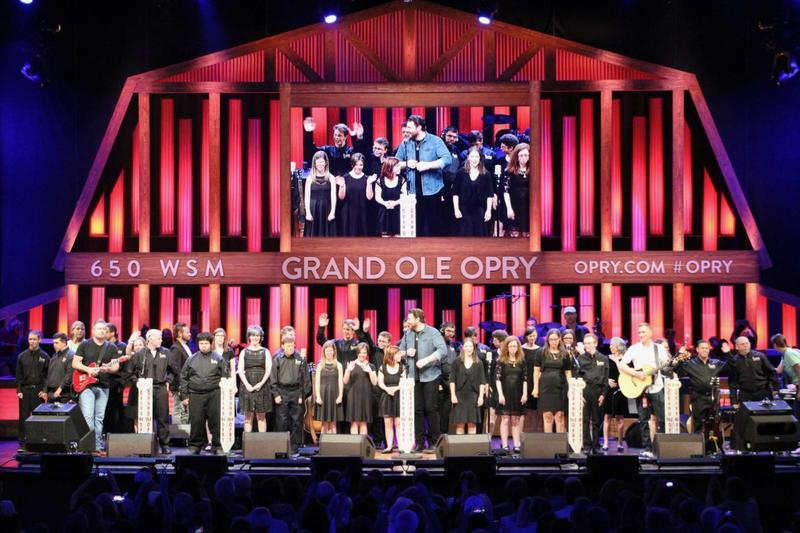 Campers from the ACM Lifting Lives music camp sing on stage at the Grand Ole Opry with country singer Chris Young.