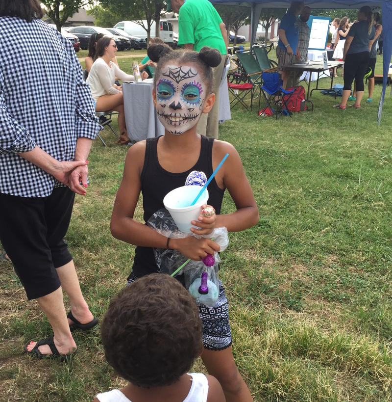 A young girl enjoys facepaint and a snowcone at the city's annual Night Out Against Crime event in the East Nashville neighborhood.