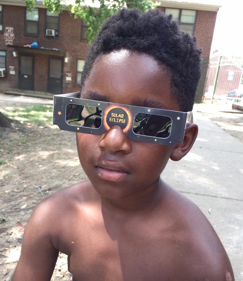 8-year-old Liteay tests out his eclipse glasses.