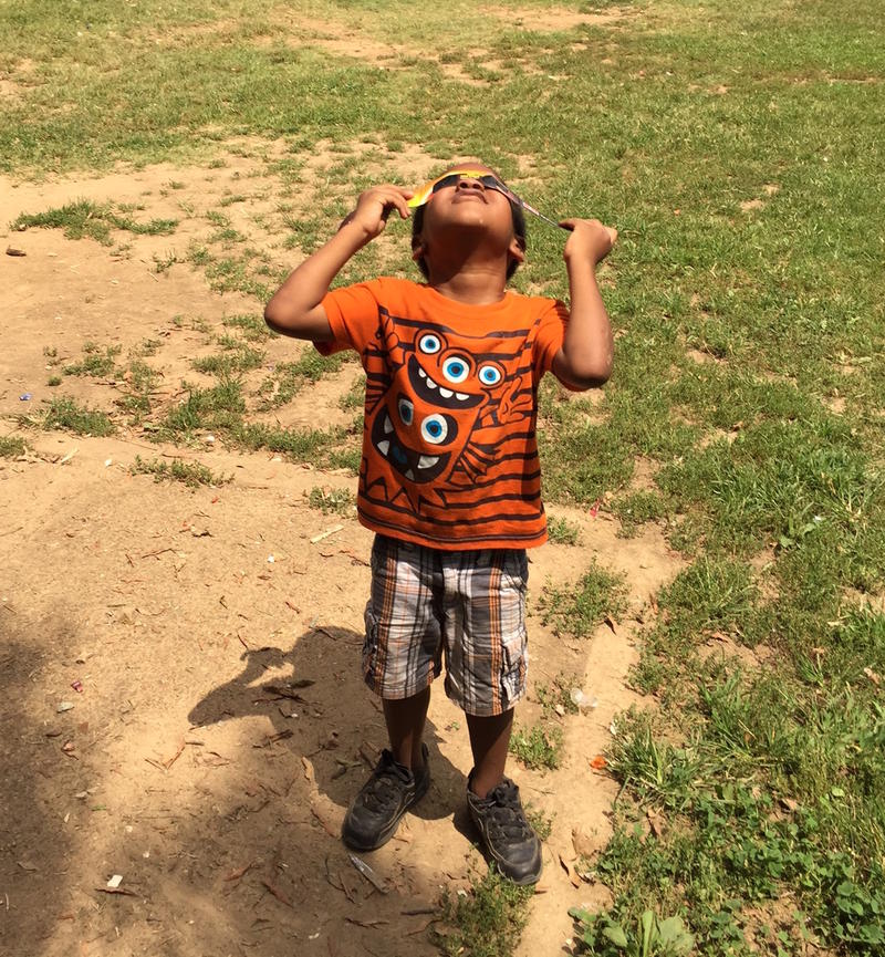 A young boy views the solar eclipse at the James Cayce Homes.