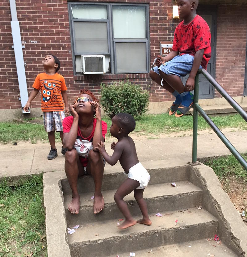 Ashton Lee, center, and her 1-year-old son, Jaquial, looks at the eclipse outside her apartment at the James Cayce Homes.