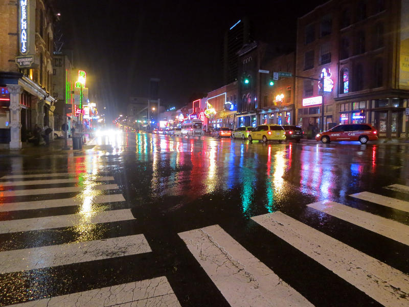 The neon lights of Lower Broadway reflect off of a wet street in Nashville, which gets 47 inches of rain a year.