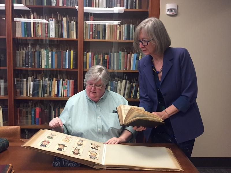 Kathleen Smith, left, peruses a volume of playing cards while university librarian Valerie Hotchkiss looks on.