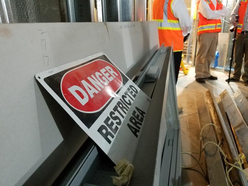 A danger sign lies up against a corridor as crews finish up reconstruction of the Cordell Hull Building.