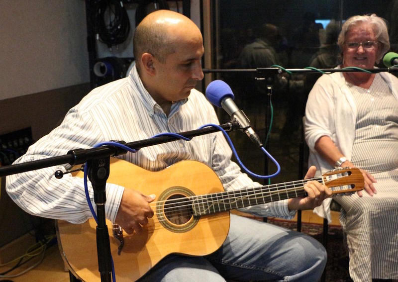 Manuel Delgado shows off a handmade nylon-string classical guitar at the live taping of Movers & Thinkers.