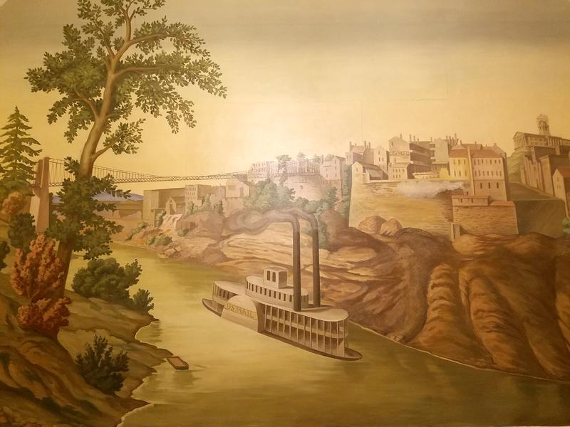 The largest mural in the cycle shows Nashville in the mid-19th century, during construction of the Tennessee State Capitol. An image of a mother goddess appears in the outcrop to the right of the steamboat's smokestacks.