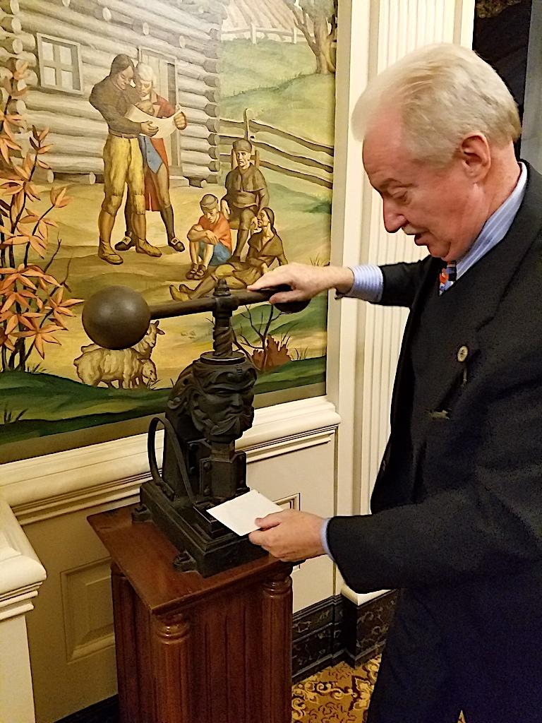 Curator Jim Hoobler demonstrates the state's official die and press, which produces the official seal. The machine dates back to before the Civil War.