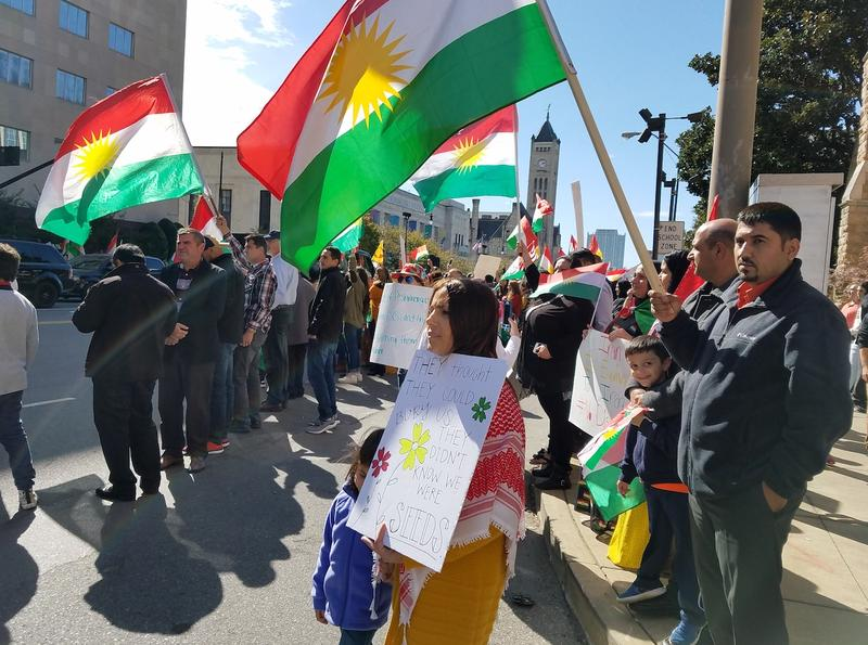 Peyman Noman holds a placard and her niece's hand during a rally of Kurdish independence supporters in downtown Nashville.