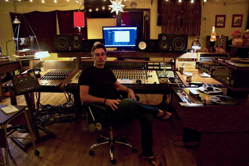 Chris Mara sits at his desk in his recording studio. On the far right is an MCI tape machine.
