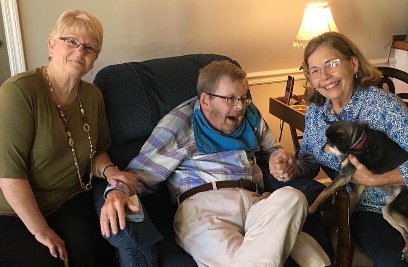 Senior volunteer caregiver Vicky Cain (left) jokes that Susan Reed (far right) usually has her purse ready to rush out the door when she shows up twice a week to spend time with Susan's husband Ron (center).