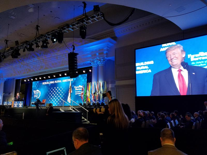 While journalists and Republican lawmakers listen from beside the stage, President Donald Trump speaks to a gathering of the American Farm Bureau Federation.