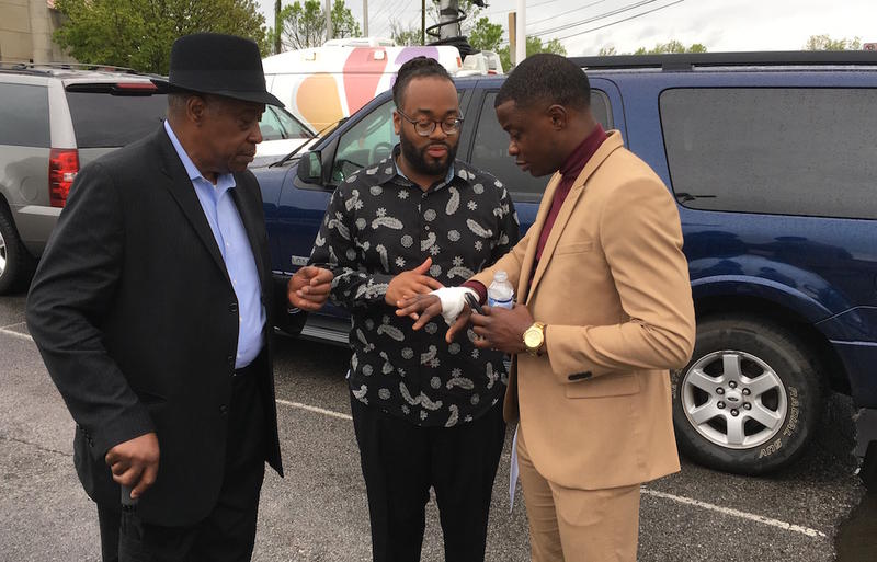 After speaking at a police news conference, James Shaw shows his bandaged hand to Rev. Aaron Marble and his father, James Shaw, Sr.