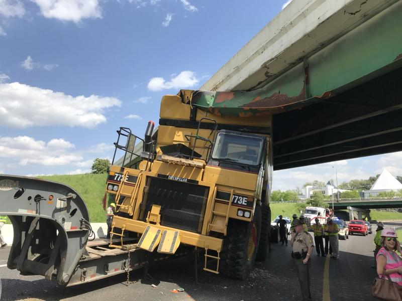 This construction vehicle, being moved by DG Equipment Movers, sliced into a beam of the I-40 overpass, coming to an immediate hault. Engineers have to support the bridge before moving the truck.