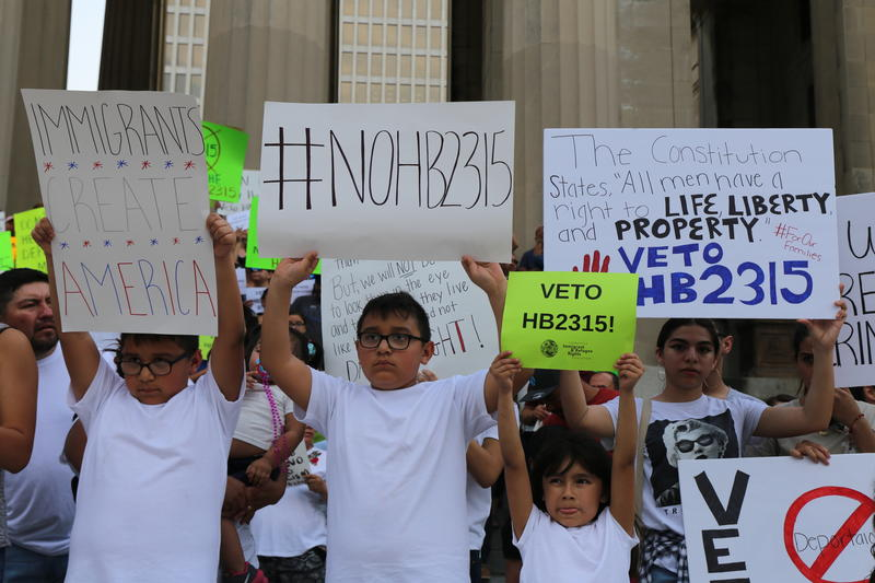 A group of children hold signs urging Gov. Haslam to veto an anti-sanctuary city bill which opponenents say could basically turn all law enforcement officers into federal agents — even inside schools.