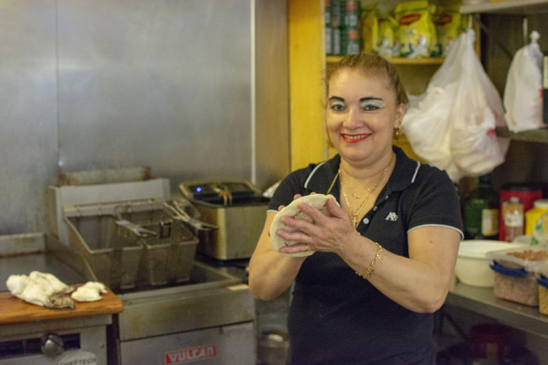 Reina Arévalo making pupusas at her restaurant.