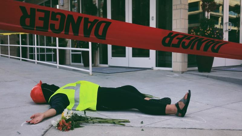 A worker lays on the floor within a chalk outline oustide the building where Fausto Flores fell to his death from the 4th floor. Moments earlier, across the street, a speaker called out the name of workers who've died in Nashville area construction sites.
