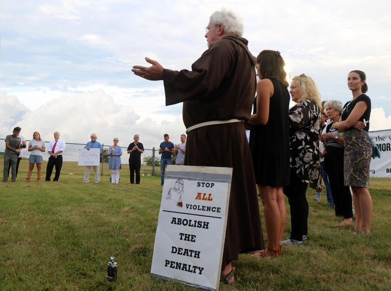 Father John Boylan leads a prayer circle before Billy Ray Irick's death.