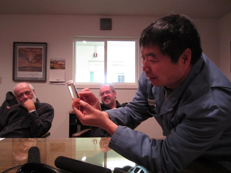 Engineer Yulong Zhang shows off a vial of pure methanol in the board room at the Western Research Institute, with Vijay Sethi (left) and Thomas Barton (center).