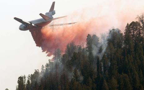 A DC-10 air tanker drops its load of fire retardant as the the Horsethief Canyon Fire continues to burn near Jackson, Wyo., on Wednesday, Sept. 12, 2012.