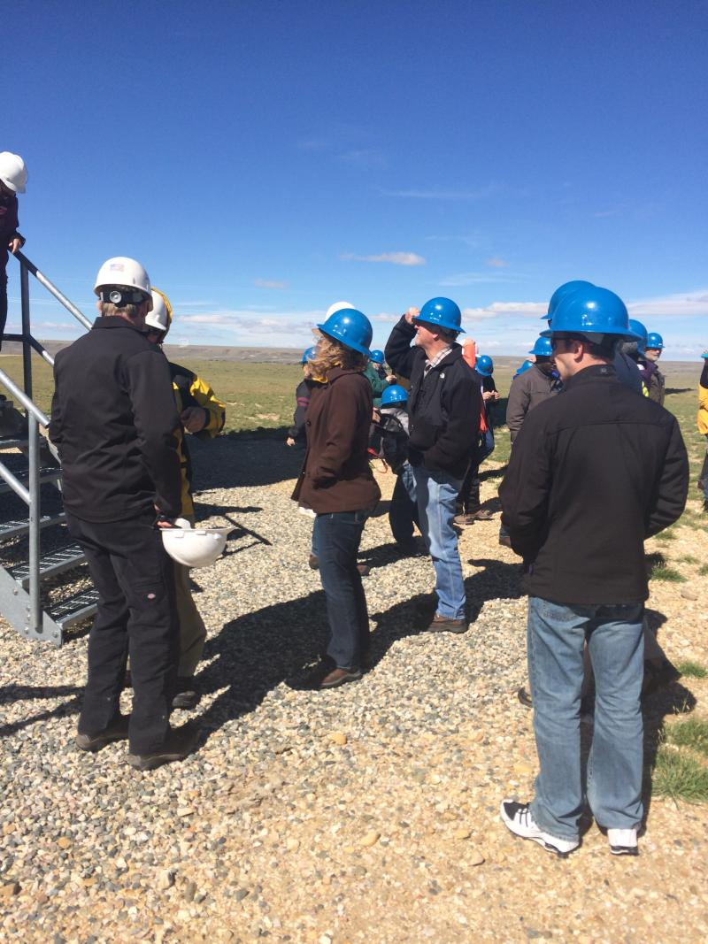 People clutch hard hats in strong winds at the High Plains Wind Farm.