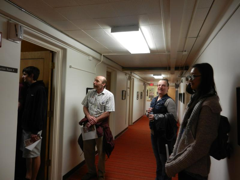 Bob Kubicheck and Yelena O'Brien watch as their students tour Wyoming Public Radio recording studios.