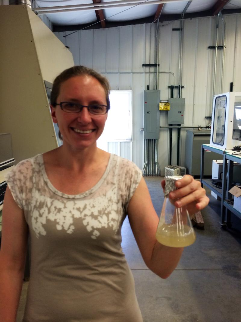 Karen Wawrousek holding up a flask of chemoautotrophic (CAT) bacteria. The bacteria eat carbon dioxide and convert it to biodiesel.