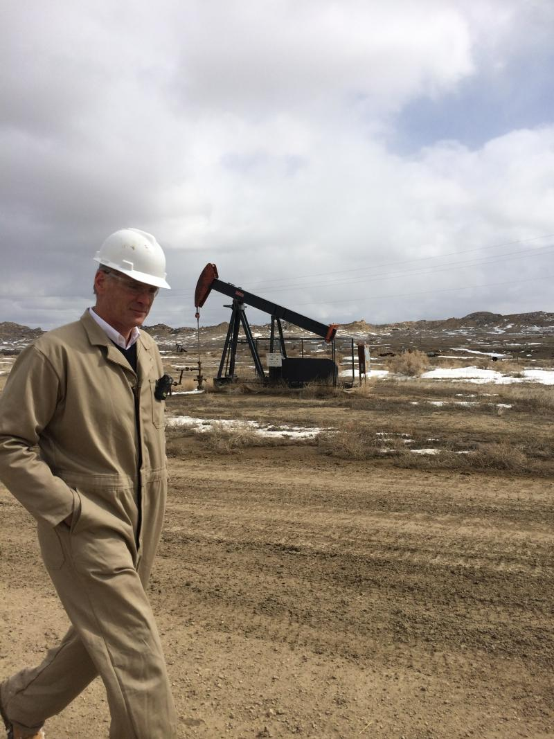 Clarke Turner, Director of the Rocky Mountain Oil Field Testing Center at Teapot Dome oil field, with a pumpjack in the background.