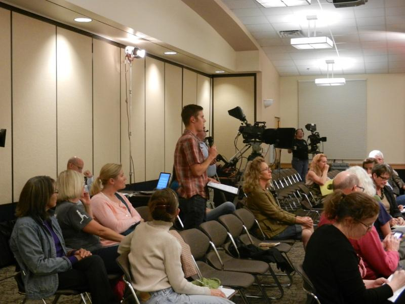 An audience member at the forum asks a question to the panel.