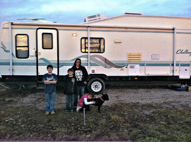 Tristan, Clay, Rachel and Miley Foshee with their dog Harley in front of the new larger RV they've just moved into.