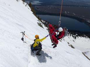 AJ Wheeler, an E.R. doctor and Teton County Search and Rescue member, aids injured skier Jesse Stover, suspended in a litter, as both men are helicoptered off Teewinot Mountain.