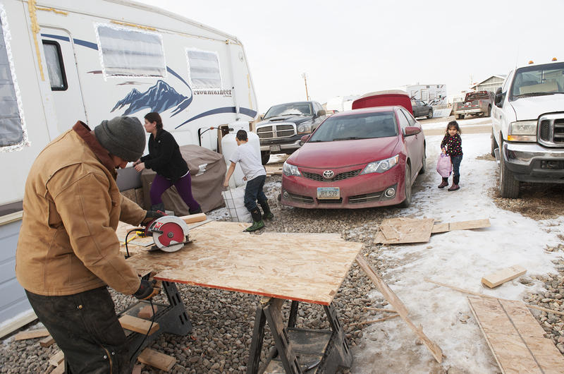 """Javier Moran, left, cuts plywood to build a """"skirt"""" surrounding his family's RV while his wife and two children prepare to use the Fox Run RV park's laundry room in Williston, North Dakota. Skirting, often built with plywood and insulated with foam, is ke"""