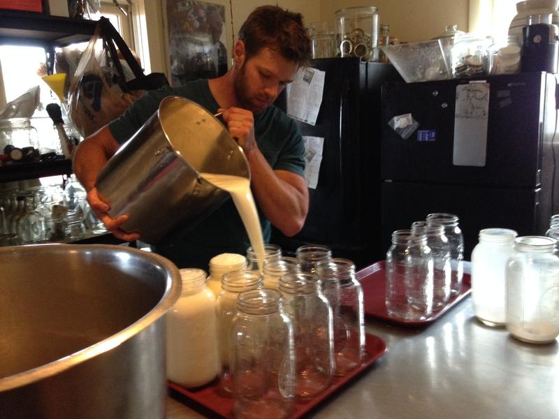 An intern filters and cools the milk in a stainless steel kitchen