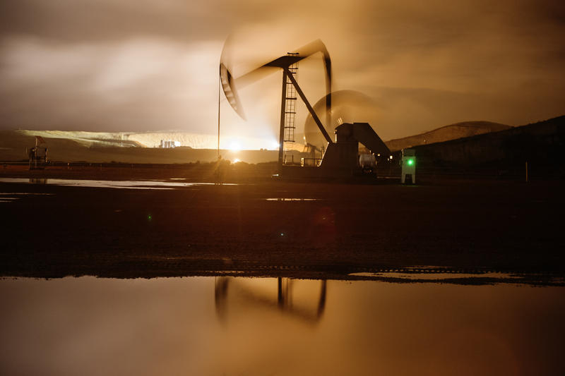 A pumpjack works throughout the night, bathed in the light from flares and electric lights on oil well pads near Watford City, North Dakota, which also illuminate low-hanging clouds.