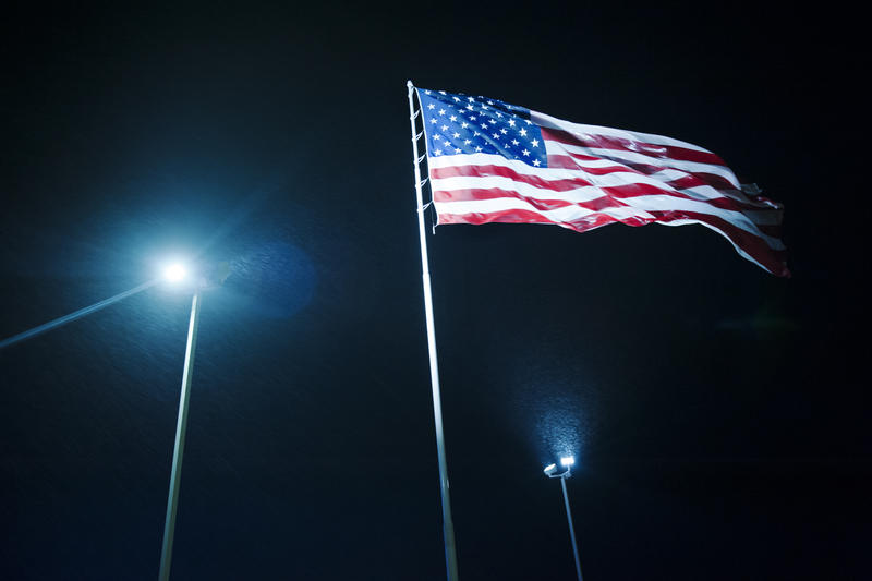 An American flag is brightly lit at a truck stop near Alexander, North Dakota. Upward-facing electrical lights are a primary cause of light pollution in oil and gas fields.