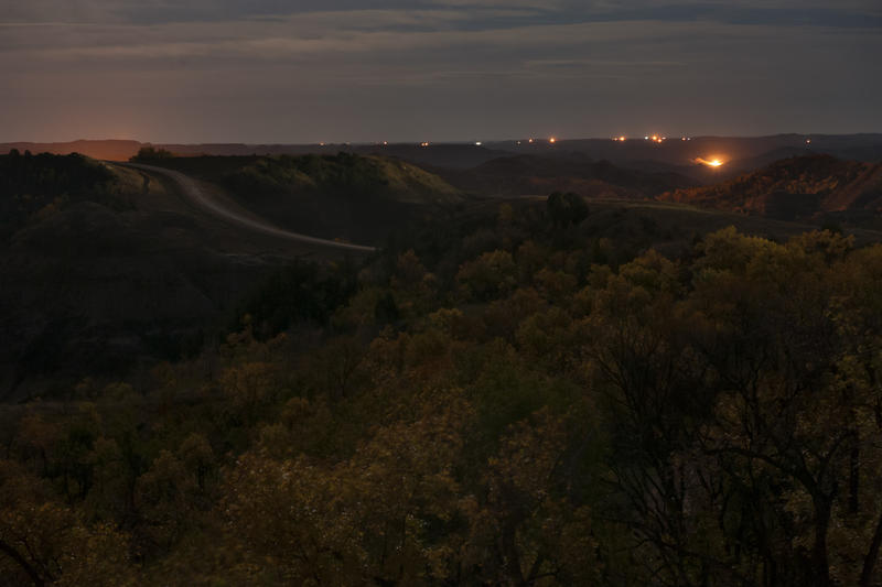 Flares and electric lights from numerous oil wells are visible on the horizon from the edge of the Little Missouri State Park in western North Dakota.