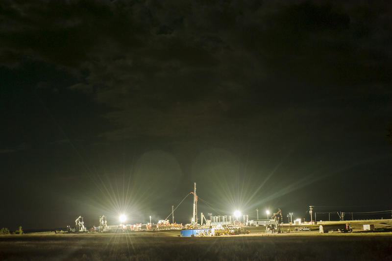 Bright lights shine on an oil well in development where activity continues throughout the night near the Little Missouri State Park in western North Dakota.