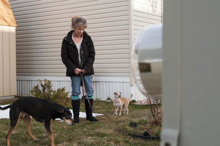 Shellberg walks her dogs near the new electric meter installed as part of her switch to the pre-paid electricity program offered by Poudre Valley REA.