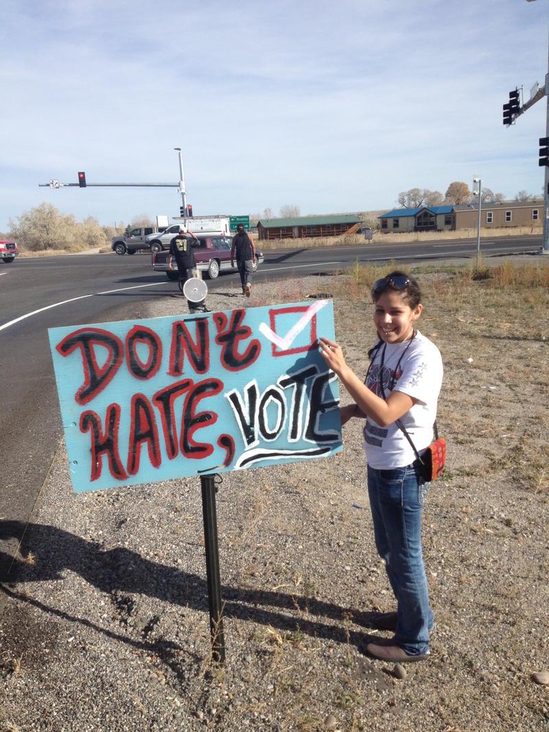 WRNAC volunteer placing signs encouraging voting on the Reservation.