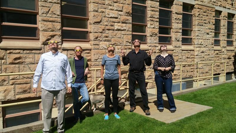 Wyoming Public Radio staff members in semi-darkness viewing partial eclipse this morning in Laramie outside the University of Wyoming campus.