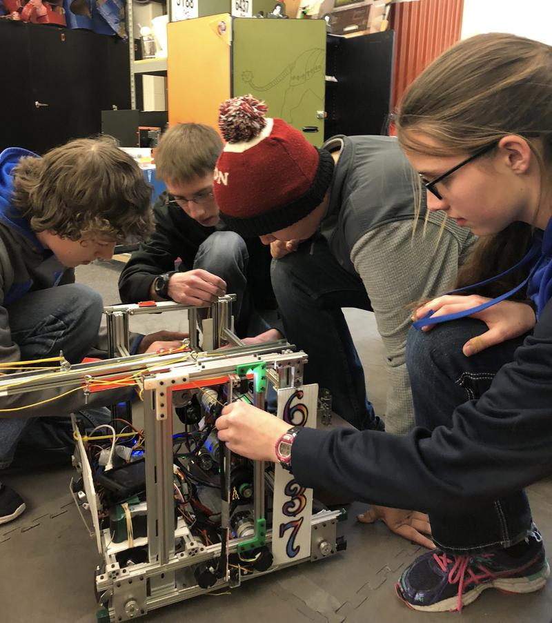 Alan Merritt and his teammates fix their robot.