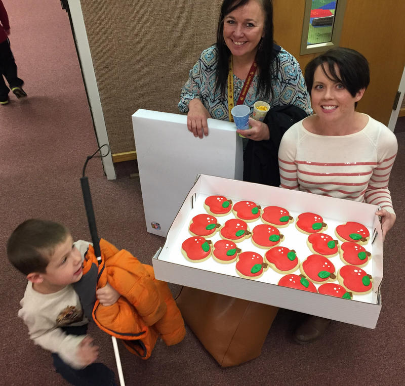 Jack, his mom Sarah Chatfield and his teacher Tia Reed pose with the cookies he's brought for the teachers at his IEP meeting. A team works with Jack and his family to create an individualized learning plan to accommodate his low vision.