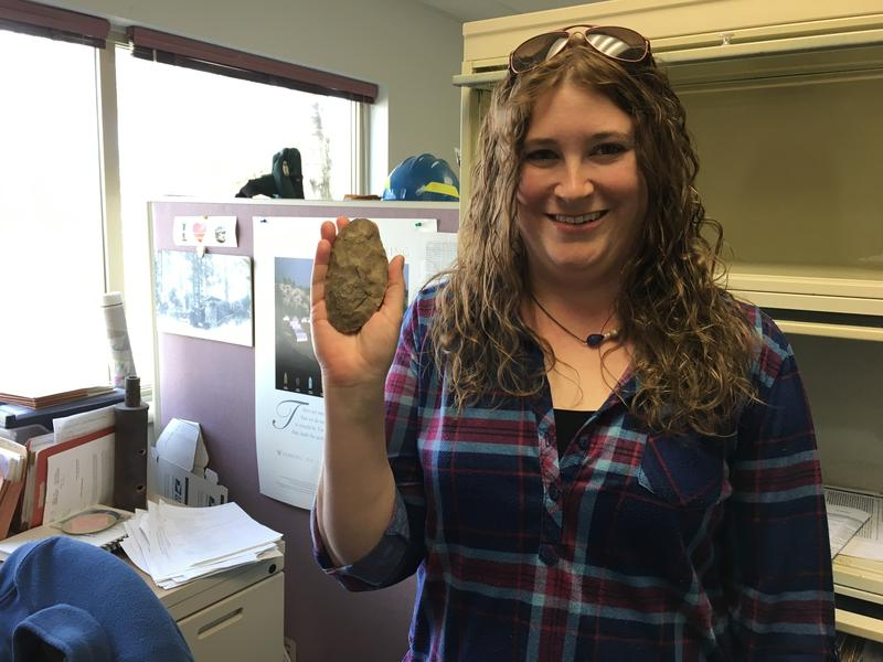 Archaeologist Tara Hamilton with a stone cutting tool found in a fire line last summer.
