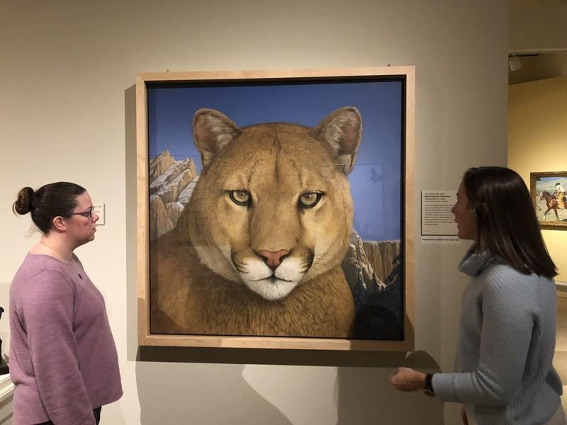Karen McWhorter, Scarlett Curator of Western American Art for the Buffalo Bill Center of the West and her curatorial assistant, Nicole Harrison, stand in front of the painting by Tom Palmore, Where Elegance Meets Fear.