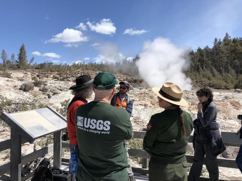 Mike Poland, the director of the Yellowstone Volcanic Observatory, Morgan Warthin, Yellowstone public affair specialist, and a member of the United States Geological Survey, stand in front of Steamboat geyser.